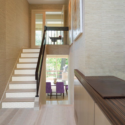 Escalier classique en bois décoré par des stickers adhésifs blancs et or représentant des hexagones en 3D