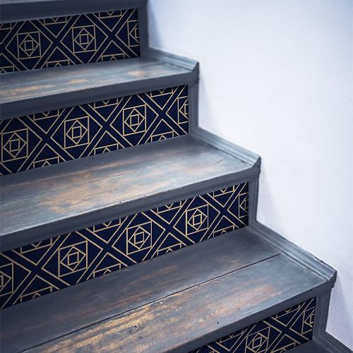 Stickers autocollants décoratifs représentant des formes couleur or sur fond bleu collés sur des contremarches en bois noir