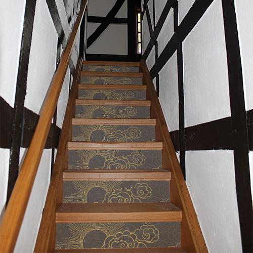 Escalier traditionnel décoré avec des stickers gris et or représentant le soleil caché par des nuages