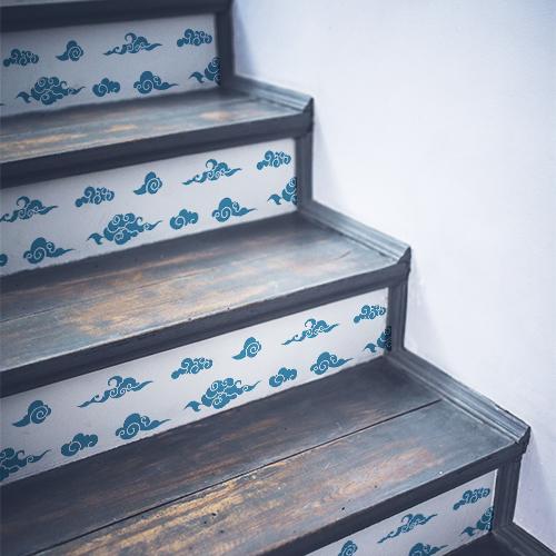 Escaliers en bois noir avec des stickers blancs ornés de nuages bleus collés dessus