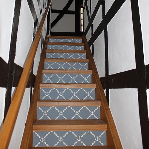 Maison traditionnelle dont les escaliers sont mis en valeurs avec des stickers autocollants représentant des ancres blanches sur fond bleu