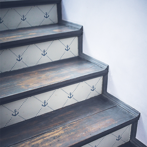 Frises d'ancres bleues sur fond blanc posées sur un escalier en bois noir