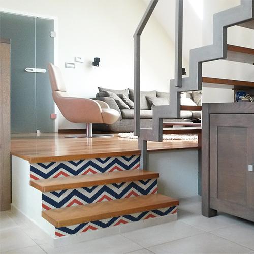 Stickers décoratifs autocollant chevrons bleus blancs rouges collés sur les contremarches d'un escalier en bois moderne