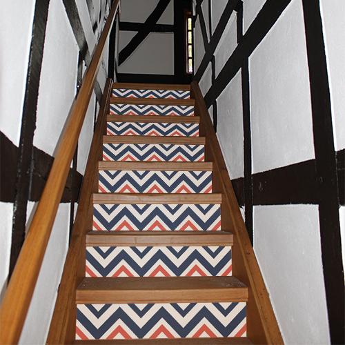 Escalier traditionnel dont les contremarches sont décorés par des stickers autocollants chevrons bleus blancs rouges