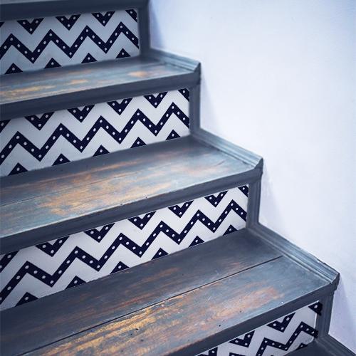 Stickers autocollants décoratifs bleus et blancs collés sur des escaliers en bois noir dans une maison traditionnelle