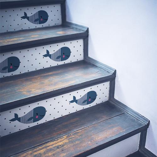 Escalier en bois noir orné de plusieurs stickers pour enfants représentant des baleines