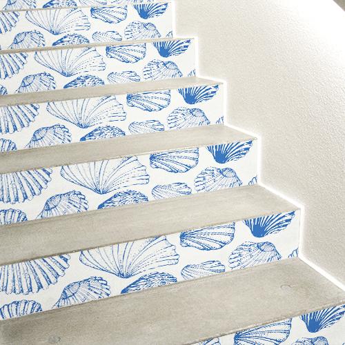 Stickers décoratifs coquilles St Jacques bleues sur fond blanc collés sur des escaliers en béton blanc