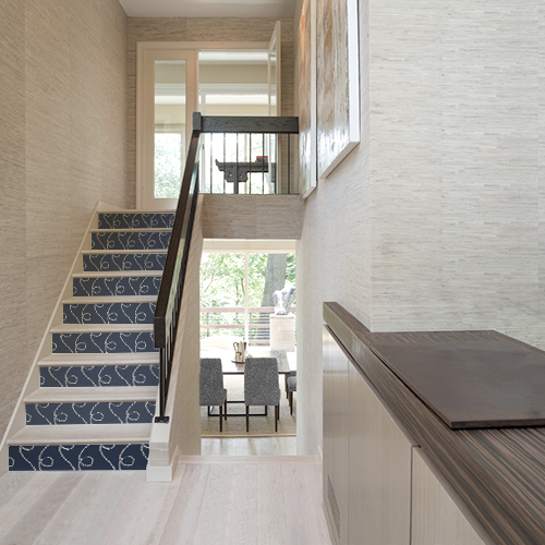 Maison moderne dont les escaliers sont ornés de stickers adhésifs représentant des cordes blanches sur fond bleu