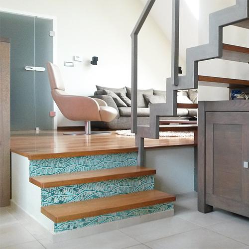 Maison moderne avec des escaliers en bois ornés de stickers adhésifs représentant des vagues bleues claires