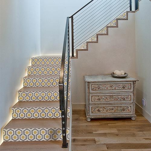 Maison moderne avec des stickers ruches grises et jaunes collés sur les contremarches de l'escalier