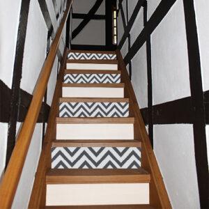 Dans une maison avec solives en vois style normande escalier de bois clair avec contremarches adhésives autocollante 1 sur deux avec motifs lignes triangulaires bleues
