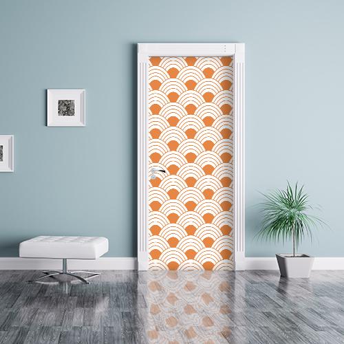 Pièce à vivre avec des murs bleus et un sticker autocollant écaille de poisson orange collé sur la porte