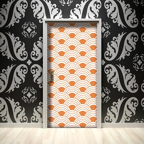 Mur noir mis en valeur par les écailles de poissons oranges collées sur la porte