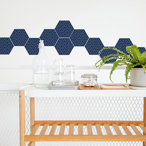 Décor scandinave avec adhésifs nid d'abeille bleu en frise et une table roulante en bois et plastique blanc.