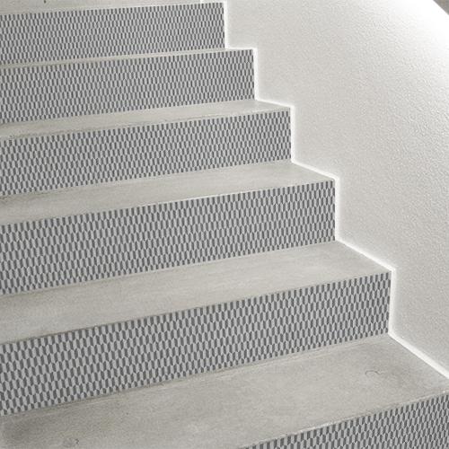 Tiroirs de commode et décoration d'escalier avec des stickers adhésifs de contremarches chevrons 3D gris et blanc.
