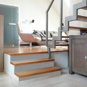 Escalier en bois clair personnaliser avec des stickers pour contremarches d'escalier au motif chevrons 3D en gris et blanc.
