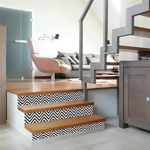 Un escalier en bois clair est personnalisé avec des contremarches adhésives graphiques représentant des chevrons en noir et blanc.