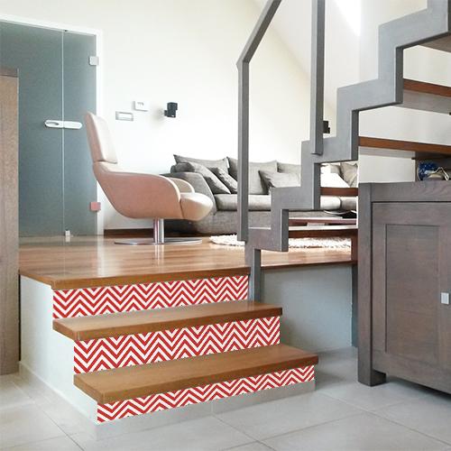 Un escalier en bois clair est sublimé par le design géométrique à chevrons des contremarches adhésives pour escalier rouge et blanc.