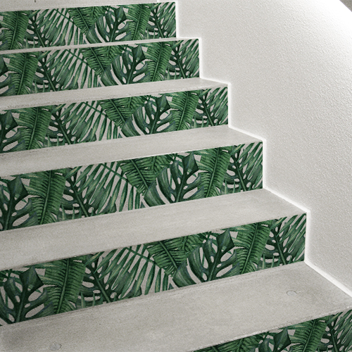 Un escalier moderne se personnalise facilement avec des adhésifs pour contremarches d'escaliers au motif exotique de feuilles tropicales vert et blanc.
