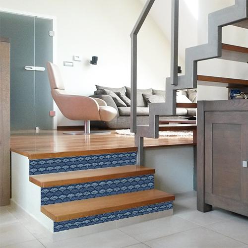 Les escaliers en bois clair sont personnalisés avec l'aide de jolies contremarches adhésives écailles sirène en camaïeu de bleu.