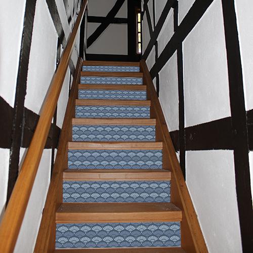 Un escalier en bois foncé se rénove simplement avec les contremarches adhésives écailles sirène bleu.