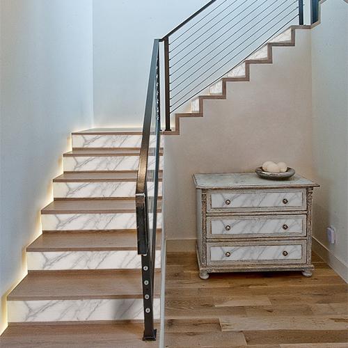 Décoration des contremarches d'escalier avec des adhésifs effet marbre blanc et personnalisation des tiroirs de commode assortis.