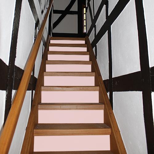 Un escalier rustique en bois foncé est rénové avec des contremarches adhésives unies rose pâle pour rendre la déco d'escalier plus lumineuse en toute simplicité.