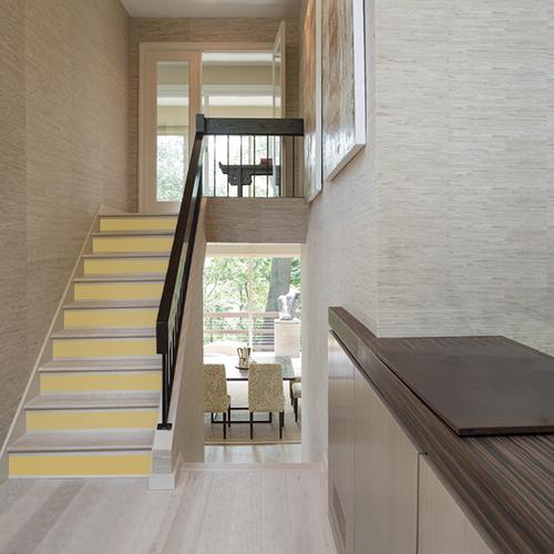 Un escalier moderne illuminé par des contremarches d'escalier adhésive aux tons jaune curry.