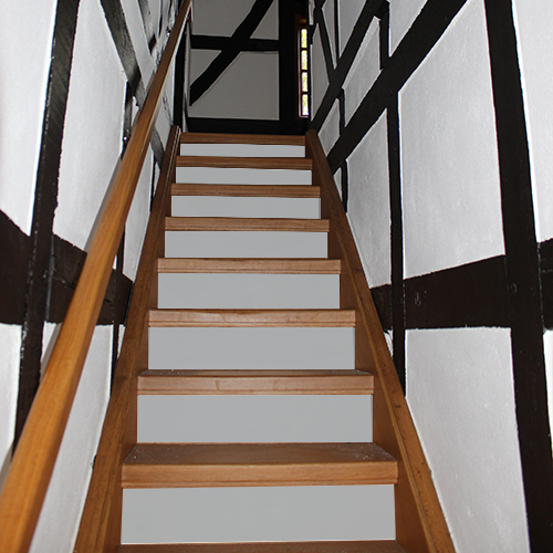 Rénover un escalier rustique en bois foncé à petit budget c'est facile et rapide grâce aux contremarches adhésives pour escalier de couleur unie grise.