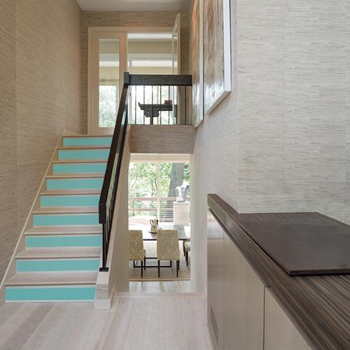 Cette déco d'escalier moderne et rehaussée de la couleur bleu canard grâce aux stickers pour contremarches d'escalier qui apportent une atmosphère apaisante à petit budget.
