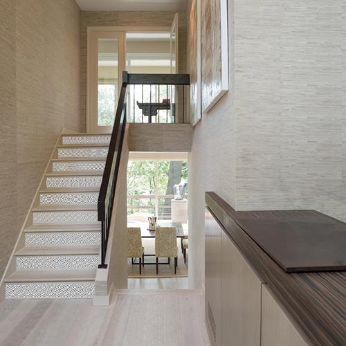 Cage d'escalier maison moderne avec contremarches personnalisées au motif ethnique losange noir et blanc.