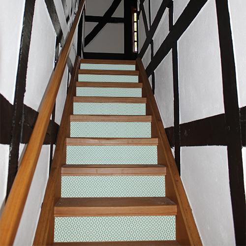 Escalier rustique rénové avec des contremarches adhésives design au motif géométrique qui sont des losanges verts imprimés .