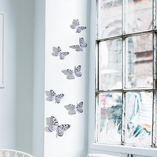 Sticker adhésif Papillons noir et blanc posé sur un mur à côté d'une fenêtre