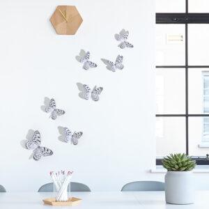 Sticker adhésif Papillons noir et blanc posé sur un mur de salon au dessous d'une horloge