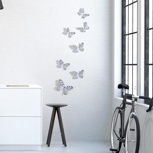 Sticker autocollant Papillons noir et blanc sur un mur blanc au dessus d'une table basse et d'un vélo