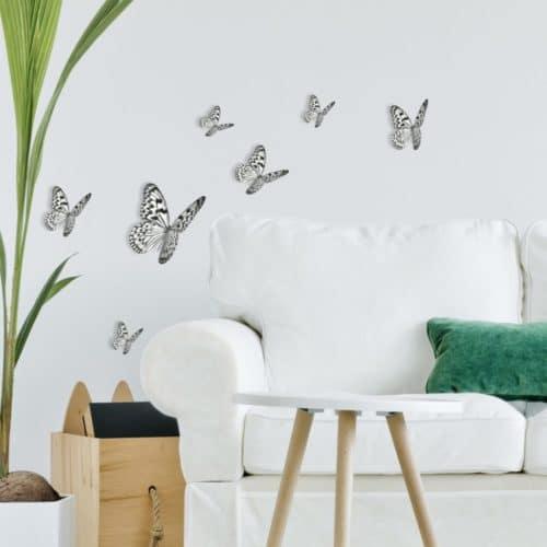 Sticker représentant des Papillons noir et blanc au dessus d'un canapé dans un salon.