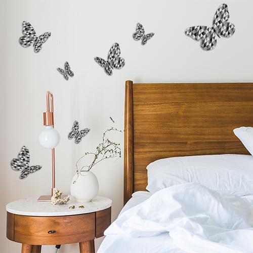 Sticker décoratif mural papillons en 3D modèle à triangles noirs et gris collé sur le mur d'une chambre à coucher