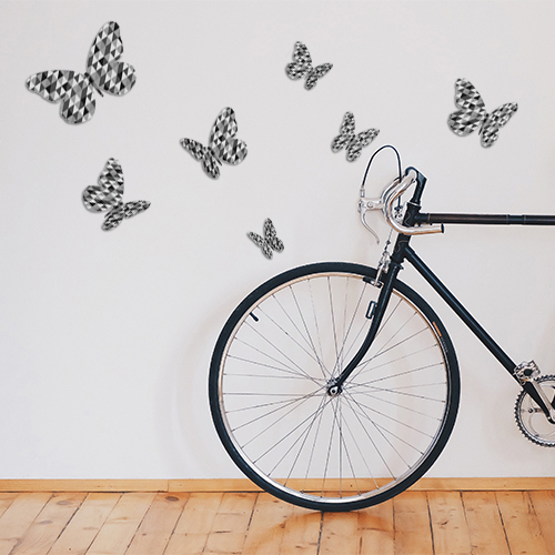 Sticker décoratif mural papillons en 3D modèle à triangles noirs et gris collés dans une pièce avec un vélo