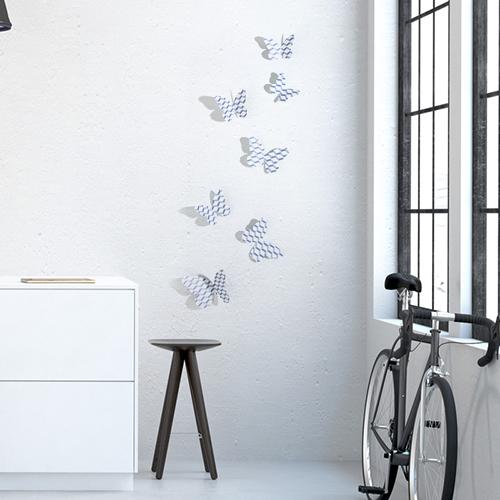 Sticker Papillons scandinave chevrons 3D sur un mur de salon avec un vélo et un meuble de salon