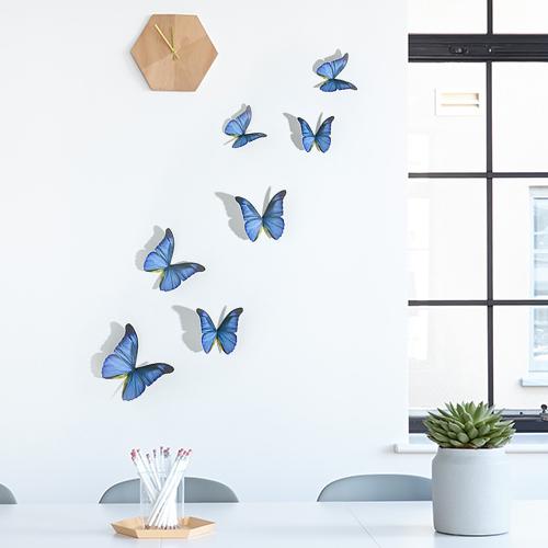 Sticker représentant des papillons bleu cobalt sur un mur blanc en dessous d'une horloge