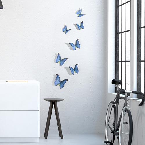 Sticker autocollant mural représentant des papillons bleu cobalt dans un salon avec un vélo et une table basse