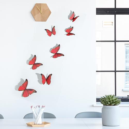 Sticker autocollant représentant des papillons rouges sur un mur blanc en dessous d'une horloge en bois