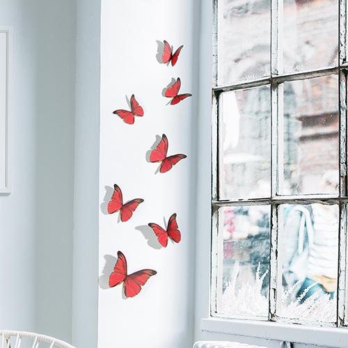 Stickers muraux représentant des papillons rouges sur un rebord de fenêtre