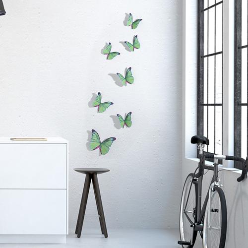 Sticker mural dans un salon avec vélo et une table basse représentant des papillons verts