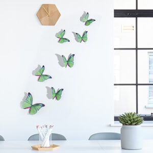 Sticker autocollant représentant des papillons verts sur un mur blanc avec une horloge en bois