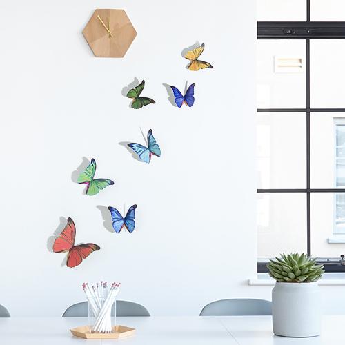 Sticker autocollant 3D en dessous d'une horloge sur un mur blanc représentant des papillons multicolores
