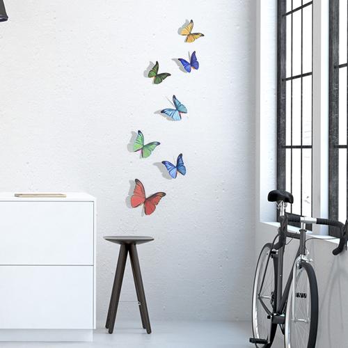 Stickers muraux Papillons multicolores déco sur un mur blanc avec un vélo
