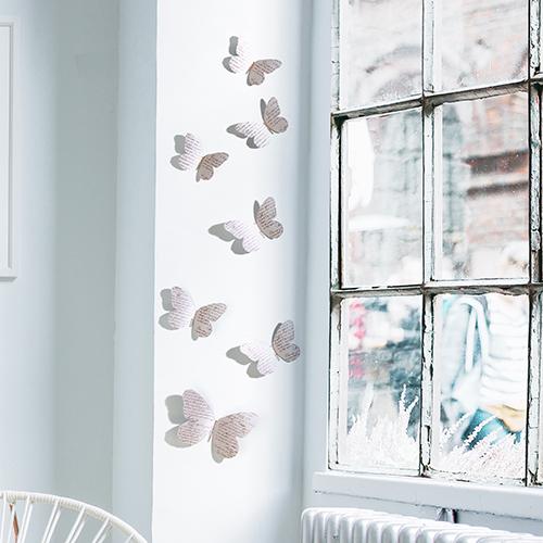 Sticker adhésif papillons manuscrits 3D sur un mur blanc sur un rebord de fenêtre