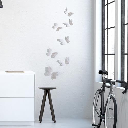 Stickers papillons manuscrits en 3D sur un mur de salon avec un vélo et une fenêtre