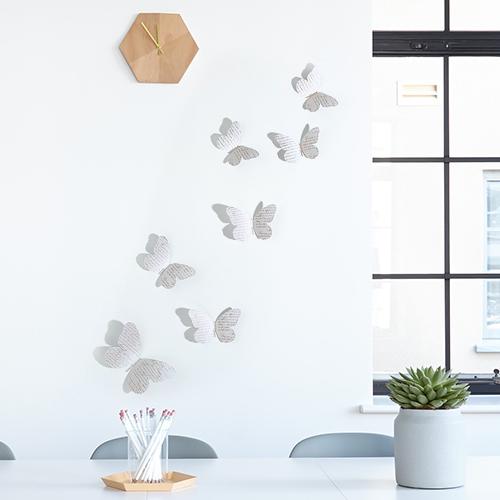 Sticker autocollant Papillons bleu et liberty sur un mur blanc à côté d'une fenêtre
